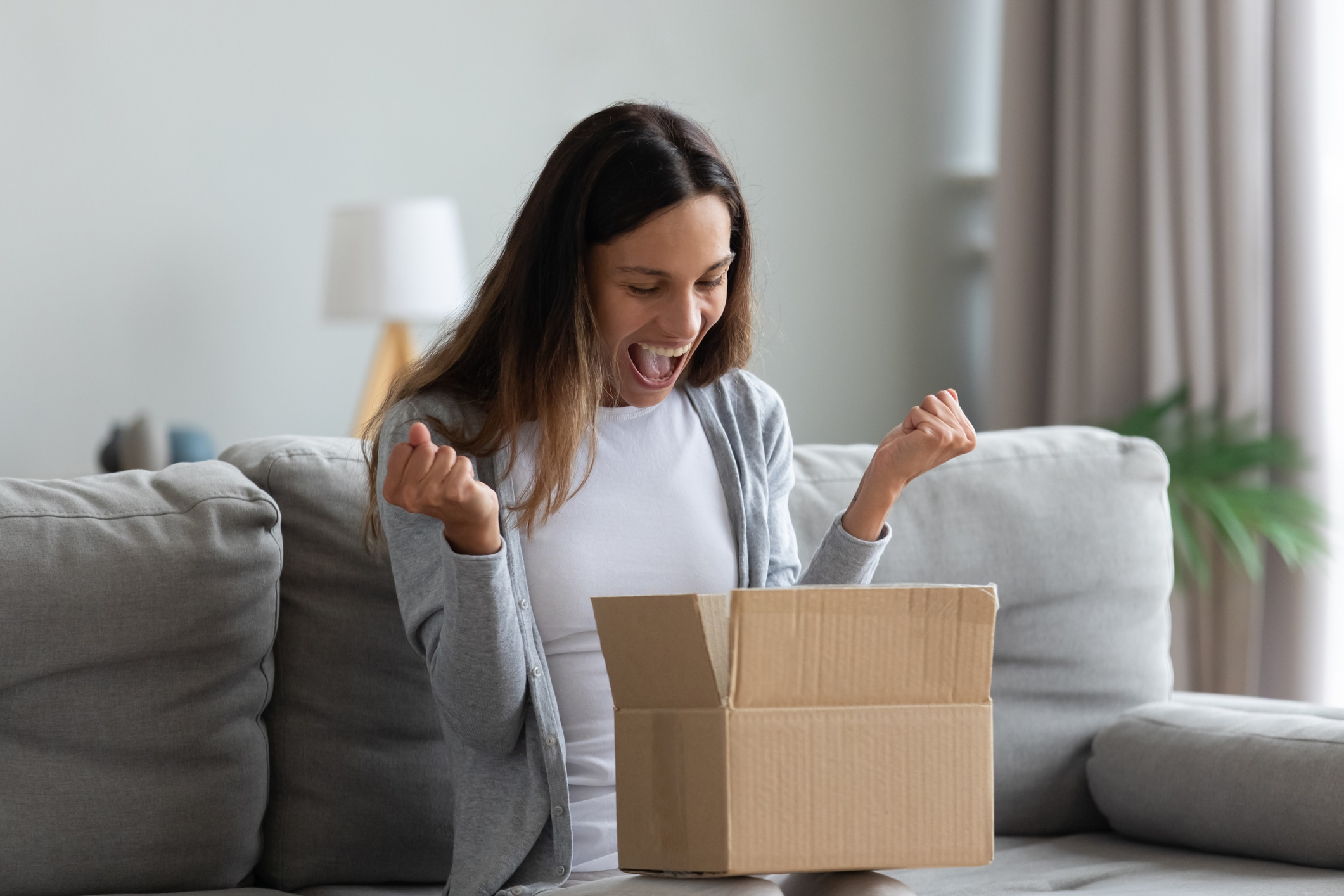 Woman opening a brown box with excitement